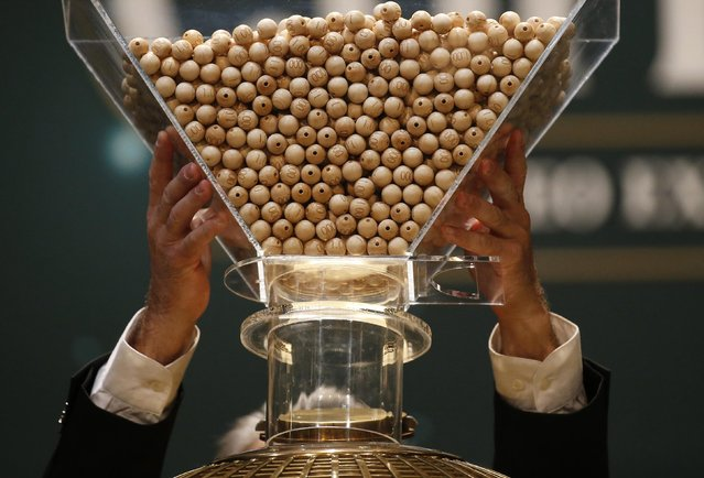 """A man puts the balls into the lottery drum before the draw for Spain's Christmas Lottery """"El Gordo"""" in Madrid December 22, 2014. (Photo by Juan Medina/Reuters)"""