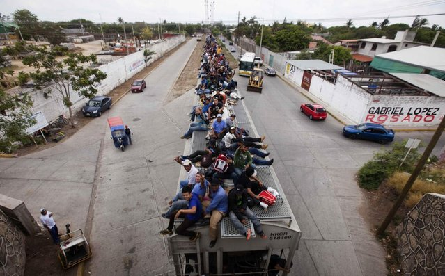 Migrants ride on top of a northern bound train toward the US-Mexico border in Juchitan, southern Mexico, Monday, April 29, 2013. Migrants crossing Mexico to get to the U.S. have increasingly become targets of criminal gangs who kidnap them to obtain ransom money. (Photo by Eduardo Verdugo/AP Photo)