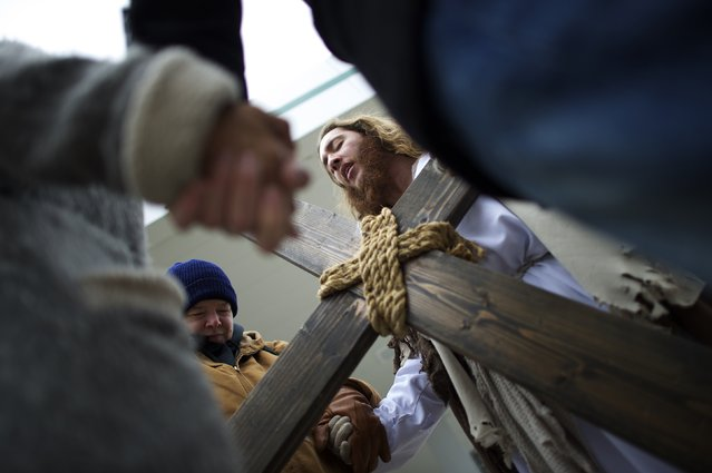 "Jayden Hensley, 39, (L) prays with Michael Grant, 28, ""Philly Jesus"", before he carried a 12 foot cross 8 miles through North Philadelphia to LOVE Park in Center City as part of a Christmas walk to spread the true message of the holiday in Philadelphia, Pennsylvania December 20, 2014. (Photo by Mark Makela/Reuters)"