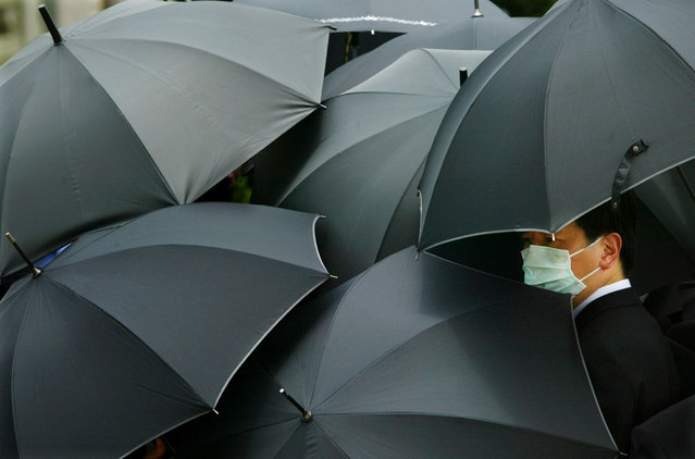 A mourner wearing a mask to ward off SARS hides under an umbrella during the funeral of SARS doctor Tse Yuen-man in Hong Kong, China May 22, 2003. (Photo by Bobby Yip/Reuters)