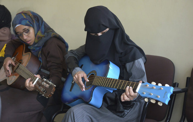 In this photo taken on Saturday, April 7, 2018, female Yemeni music students practice playing the guitar during a music class at the Cultural Centre in Sanaa, Yemen. For the young people who receive lessons from Abdullah El-Deb'y, music is a safe haven from the misery of Yemen's devastating war. El-Deb'y offers free lessons to students eager to escape the suffering caused by the war and is seeking to form a national orchestra comprised of young Yemenis. (Photo by Hani Mohammed/AP Photo)