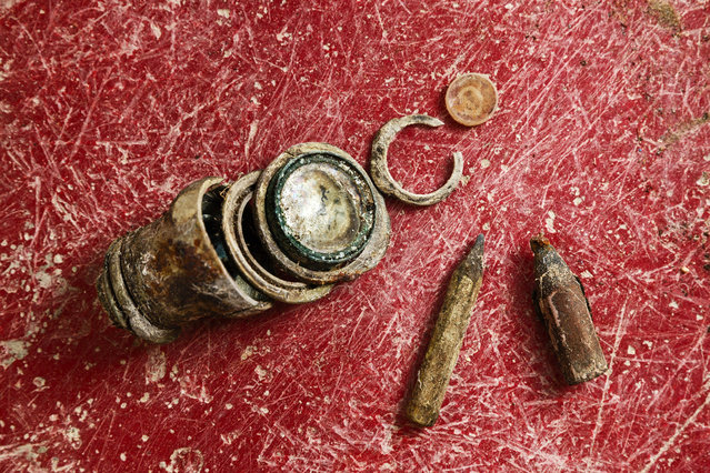 This photo taken on December 17, 2014, shows pencils and a broken monocle found during the exhumation of a mass grave of those killed by their political ideology during and after the Spanish civil war at the Puerto Real cemetery are displayed to be pictured by the photographer in Puerto Real, Spain. (Photo by Daniel Ochoa de Olza/AP Photo)