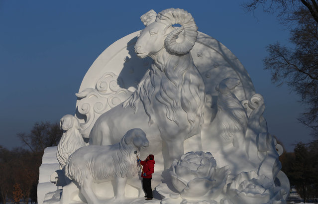 A sculptor polishes a snow sculpture in the 16th Harbin Ice and Snow World which will officially open on January 5 on December 22, 2014 in Harbin, China. (Photo by Feature China/Barcroft Media)