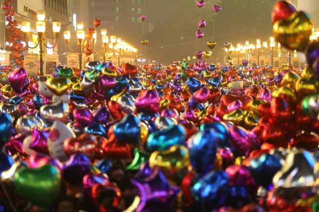 People prepare to release balloons during the New Year's Eve countdown event at Jiefangbei Pedestrian Street on December 31, 2014 in Chongqing, China. (Photo by ChinaFotoPress/ChinaFotoPress via Getty Images)