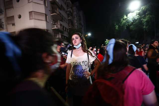 An anti-abortion activist reacts as others leave after lawmakers passed a bill that legalizes abortion, outside Congress in Buenos Aires, Argentina, Wednesday, December 30, 2020. (Photo by Marcos Brindicci/AP Photo)