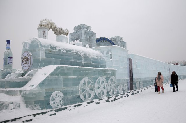 Visitors walk past a train-shaped ice sculpture ahead of the 31st Harbin International Ice and Snow Festival in the northern city of Harbin, Heilongjiang province, January 4, 2015. The winter festival will be officially opened on January 5, 2015. (Photo by Kim Kyung-Hoon/Reuters)