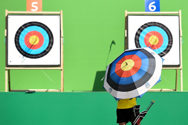 An archer holding an umbrella with a target design checks the target  during the first day of the Archery test event for the Rio 2016 Olympic Games at Sapucai Sambodrome on September 15, 2015 in Rio de Janeiro, Brazil. (Photo by Buda Mendes/Getty Images)