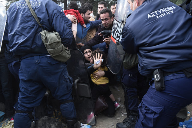 A woman tries to protect her daughter as refugees scuffle with the Greek police in their effort to reach the borderline with Macedonia, near the Greek village of Idomeni, Sunday, November 22, 2015. Over 1,000 migrants gathered in the Greek town Idomeni protested Saturday against the decision by Macedonian authorities across the border to turn away migrants who are not from war zones such as Syria, Afghanistan and Iraq. (Photo by Giannis Papanikos/AP Photo)