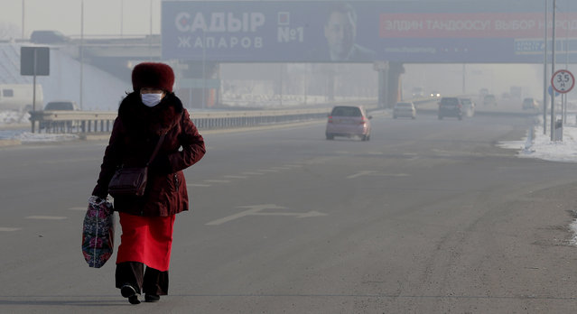 A Kyrgyz woman walks along a road in the village of Razdolnoye near Bishkek in front of a poster for presidential candidate Sadyr Dzhaparov in Bishkek, Kyrgyzstan, 07 January 2021. Presidential elections and referendum on the form of government in Kyrgyzstan will be held on 10 January 2021. (Photo by Igor Kovalenko/EPA/EFE)