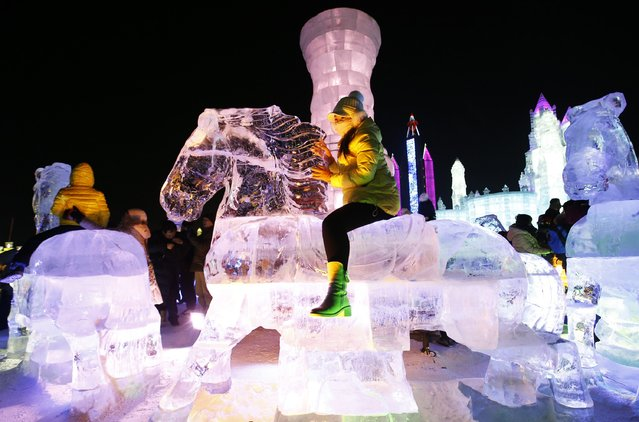 A woman rides horse-shaped ice sculpture iduring the opening day of the 31st Harbin International Ice and Snow Festival in the northern city of Harbin, Heilongjiang province, January 5, 2015. (Photo by Kim Kyung-Hoon/Reuters)