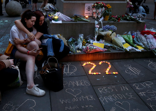 Girls sit by a memorial during the first anniversary of the Manchester Arena bombing, in Manchesterr, England on May 22, 2018. The suicide bomb attack took place following a concert at Manchester Arena by US singer Ariana Grande and claimed the lives of 22 people. (Photo by Andrew Yates/Reuters)