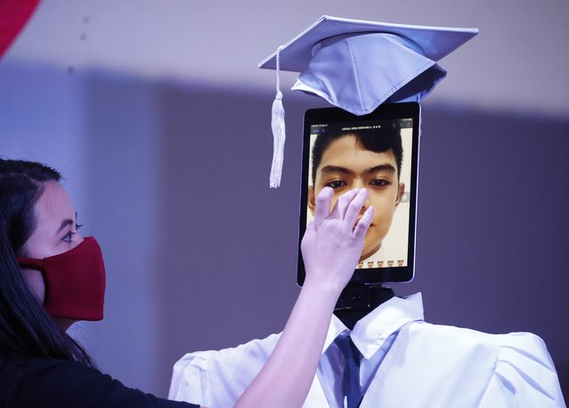 A Filipino teacher checks a picture of a student shown on a tablet that is attached to robot during a graduation ceremony at a school in Taguig City, Philippines, 22 May 2020. At least 179 high school students received their diploma during an online graduation ceremony that was beamed live on Facebook as a measure to prevent the spread of the coronavirus and COVID-19 disease. (Photo by Francis R. Malasig/EPA/EFE)