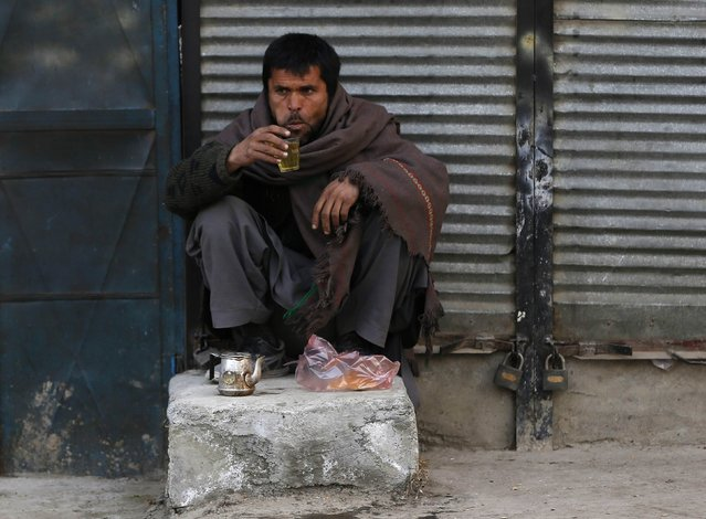An Afghan man has his breakfast at a roadside tea shop during the early morning hours in Kabul, January 11, 2015. (Photo by Omar Sobhani/Reuters)