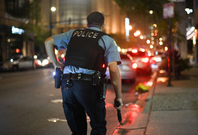A Chicago Police Officer runs toward gunfire as looters break into downtown stores in the early hours of the morning on August 10, 2020. (Photo by RMV/Rex Features/Shutterstock)
