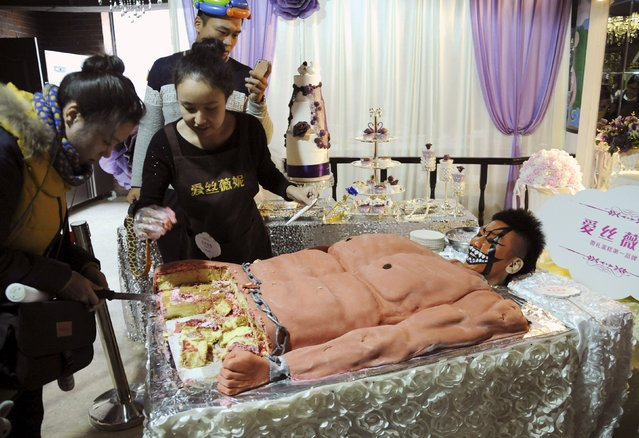 A staff member (R) looks on next to a cake, which was baked in the shape of a muscular man, for customers to try for free during a promotional event of a cake store in Shenyang, Liaoning province, China, December 6, 2015. (Photo by Reuters/Stringer)