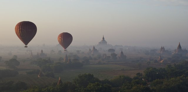 """Sunrise at Bagan"". Like in a fairytale the balloon rises over the early morning mist to reveal thousands of ancient temples which slowly reveal their gold colour in the rising sun. a moment of peace in a ratteled country. Location: Burma/Myanmar, Bagan. (Photo and caption by Wibke Helfrich/National Geographic Traveler Photo Contest)"