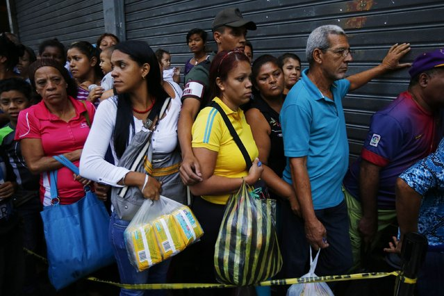 People line up to buy toilet paper and baby diapers at a supermarket in downtown Caracas January 19, 2015. (Photo by Jorge Silva/Reuters)