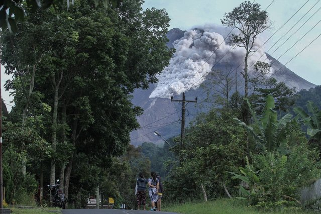 Locals walk on a road as Mount Merapi volcano spews hot ash in Kaliurang, Sleman, Yogyakarta, Indonesia, January 27, 2021. (Photo by Hendra Nurdiyansyah/Antara Foto via Reuters)