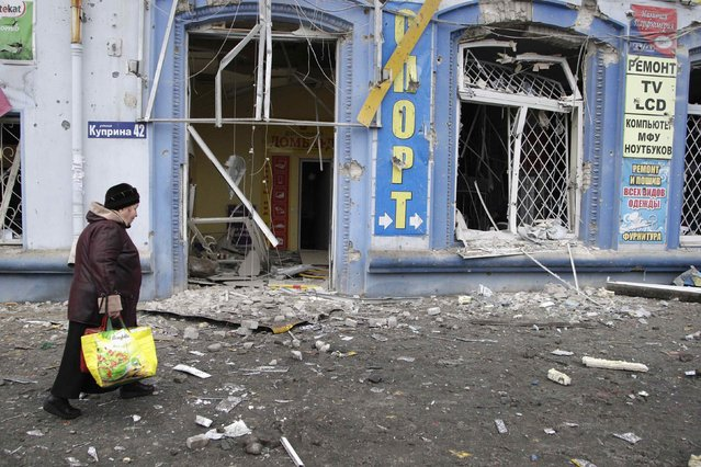 A woman walks past a damaged building near a trolleybus stop in Donetsk, January 22, 2015. (Photo by Alexander Ermochenko/Reuters)