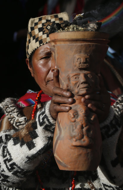 "An Andean religious leader holds an urn with burning incense in a procession of the Bolivian deity statuette ""illa of Ekeko"" as it is driven to the Alasitas Fair, in which Ekeko is the central figure, in La Paz, Bolivia, Saturday, January 24, 2015. (Photo by Juan Karita/AP Photo)"