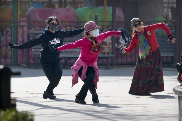 Women wearing face masks to protect against the spread of the coronavirus dance at a public park in Beijing, Friday, February 19, 2021. China has been regularly reporting no locally transmitted cases of COVID-19 as it works to maintain control of the pandemic within its borders. (Photo by Mark Schiefelbein/AP Photo)