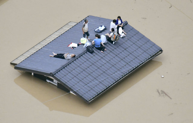 An aerial view shows local residents seen on the roof of submerged house at a flooded area as they wait for a rescue in Kurashiki, southern Japan, in this photo taken by Kyodo July 7, 2018. (Photo by Kyodo News via Reuters)