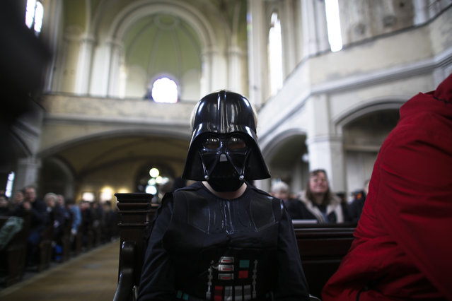 A boy dressed as the Star Wars character Darth Vader attends a Star Wars themed church service, at the  Zion Church  in Berlin, Sunday, December 20, 2015. About 500 people, some carrying light saber props or wearing Darth Vader masks, attended the service, more than twice as many as usual on a Sunday. (Photo by Markus Schreiber/AP Photo)
