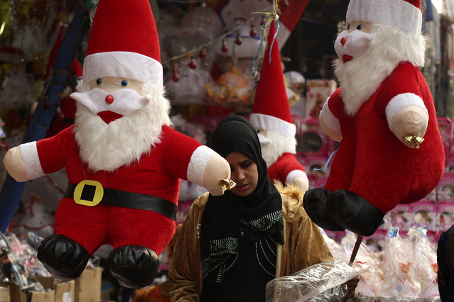 A woman looks at Santa Claus themed Christmas items at a street market in Cairo, Egypt December 21, 2015. (Photo by Asmaa Waguih/Reuters)