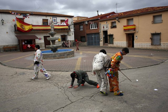 """Young believers play at the main square before heading to the cemetery to remember the deceased members of their fellow believers during the """"Endiablada"""" festival in Almonacid del Marquesado, in central Spain February 2, 2015. (Photo by Susana Vera/Reuters)"""