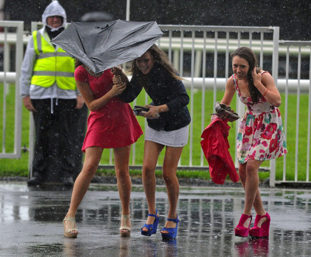 Sinead Flynn, Aine Murray,  Catherine Fearty battle against the weather during day four of the 2013 Galway Summer Festival at Galway Racecourse, Ballybrit, Ireland, on August 1, 2013. (Photo by Barry Cronin/PA Wire)