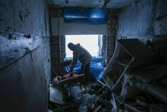 A resident covers the window of his apartment with a plastic sheet inside a residential block, that was damaged by a shelling on Wednesday according to locals, in Donetsk, February 5, 2015. (Photo by Maxim Shemetov/Reuters)