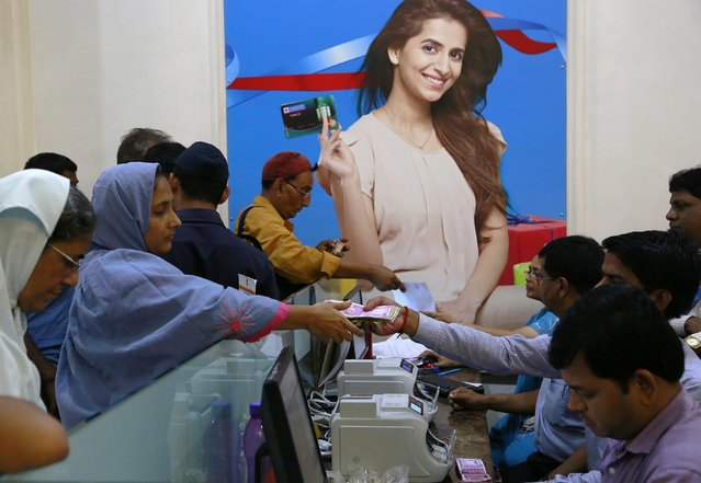 Indians exchange discontinued currency notes in a bank in Mumbai, India, Wednesday, November 16, 2016. India announced a week ago that it was withdrawing 500 and 1,000 rupee notes as legal tender to fight corruption and tax evasion. However, people are allowed a onetime swap of 4,000 rupees ($59) at any bank in exchange for smaller notes to meet immediate needs. (Photo by Rajanish Kakade/AP Photo)