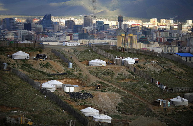 Gers, traditional Mongolian tents, are seen on a hill in an area known as a ger district in Ulan Bator June 26, 2013. (Photo by Carlos Barria/Reuters)