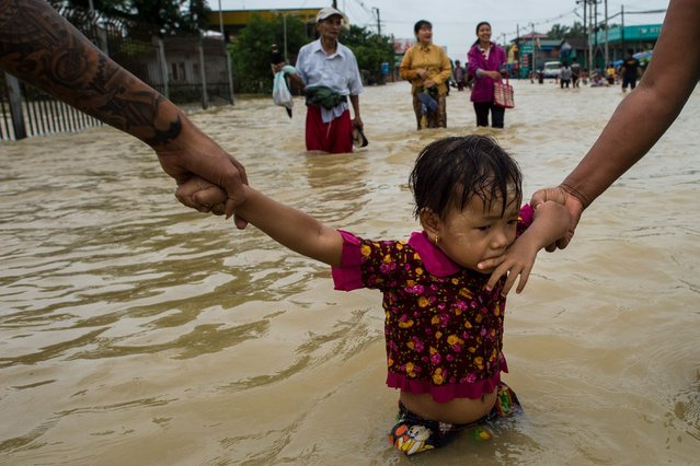Residents hold onto a child as they walk through floodwaters in the Bago region, some 68 km away from Yangon, on July 29, 2018. Heavy monsoon rains have pounded Karen state, Mon state and Bago region in recent days and show no sign of abating, raising fears that the worst might be yet to come. (Photo by Ye Aung Thu/AFP Photo)