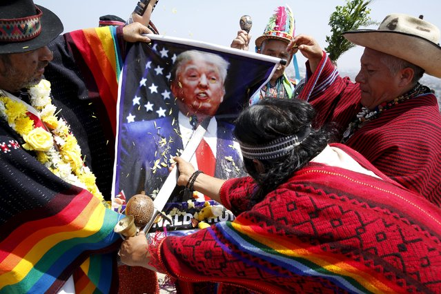Peruvian shamans holding a poster of U.S. Republican presidential candidate Donald Trump perform a ritual of predictions for the new year at Morro Solar hill in Chorrillos, Lima, Peru, December 29, 2015. The ritual is an end-of-the-year tradition and the shamans called for world peace and wished good luck for the upcoming elections in Peru and the U.S. (Photo by Mariana Bazo/Reuters)