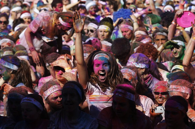 A woman dances after finishing the Colour Run at Centennial Park in Sydney August 25, 2013. According to organizers, 15,000 runners registered to complete the 5km (3 miles) course in Centennial Park on Sunday, being covered in blue, pink, orange and yellow powder on their way to the finish line. (Photo by Daniel Munoz/Reuters)