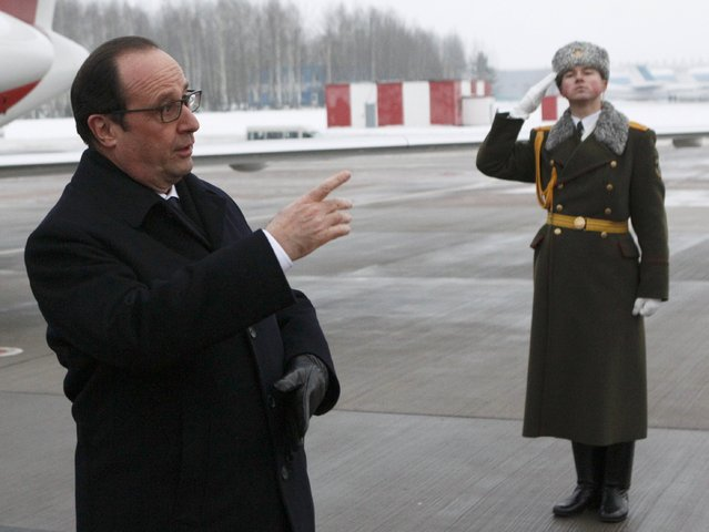 France's President Francois Hollande (L) reacts as he takes part in a welcoming ceremony upon his arrival at an airport near Minsk, February 11, 2015. (Photo by Valentyn Ogirenko/Reuters)