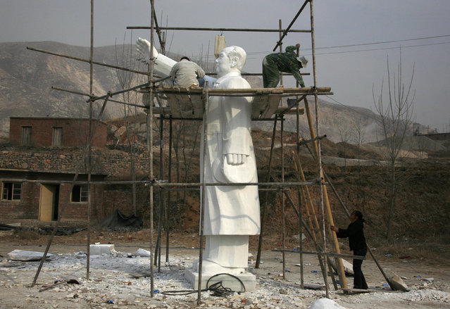 Sculptors work as they stand on scaffolding surrounding a statue of Mao Zedong in the town of Dangcheng,  southwest of Beijing, March 23, 2009. (Photo by David Gray/Reuters)