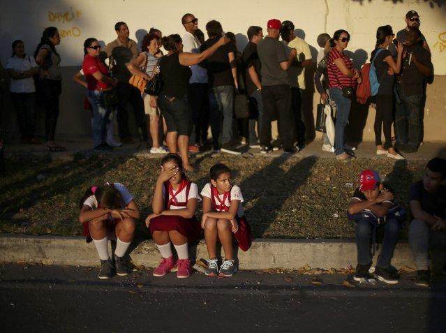 Students rest as people wait in line to pay tribute to Cuba's late President Fidel Castro in Havana, Cuba, November 28, 2016. (Photo by Edgard Garrido/Reuters)