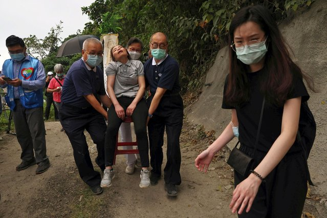Members of the Tzu Chi Foundation help a grieving woman as relatives of the victims mourn near the site a day after the deadly train derailment at a tunnel north of Hualien, Taiwan on April 3, 2021. (Photo by Ann Wang /Reuters)