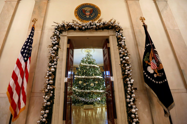 The White House Christmas Tree is seen through the doorway into the Blue Room during a preview of holiday decor at the White House in Washington, U.S., November 29,  2016. (Photo by Kevin Lamarque/Reuters)
