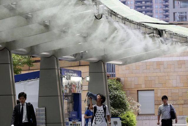 People cool down under the cooling mist spot in Tokyo, Monday, July 23, 2018. Searing hot temperatures are forecast for wide swaths of Japan and South Korea in a long-running heat wave. The mercury is expected to reach 39 degrees Celsius (102 degrees Fahrenheit) on Monday in the city of Nagoya in central Japan and reach 37 (99 F) in Tokyo. (Photo by Koji Sasahara/AP Photo)