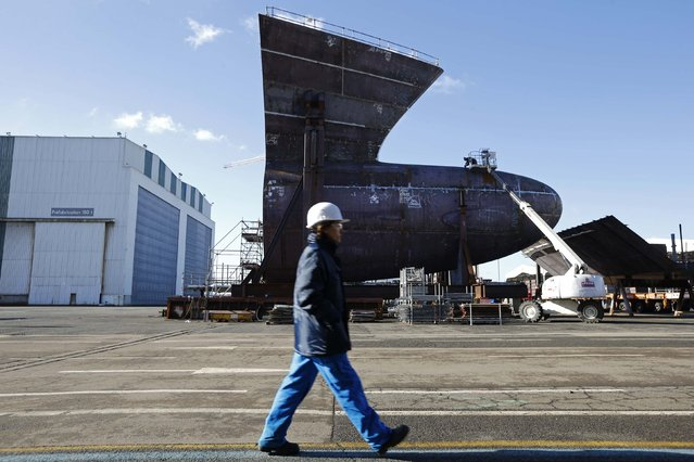 A ship builder walks past a section of the Oasis Class 3 cruise ship at the STX Les Chantiers de l'Atlantique shipyard site in Saint-Nazaire, western France, February 17, 2015. The Oasis-class III vessel is scheduled for delivery in mid-2016. (Photo by Stephane Mahe/Reuters)