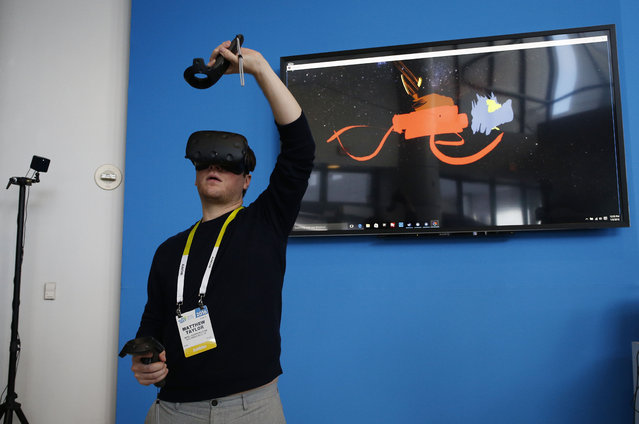 Matthew Taylor paints in 3D virtual reality at the Intel booth using HTC Vive virtual reality goggles at CES International, Wednesday, January 6, 2016, in Las Vegas. (Photo by John Locher/AP Photo)