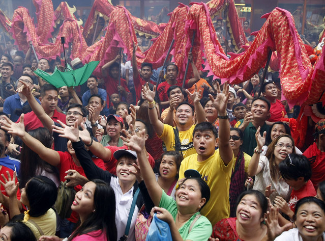 Filipinos try to catch sweets and giveaways being thrown at them following dragon and lion dance performances in front of a supermarket at Manila's Chinatown district of Binondo to celebrate the Chinese New Year Thursday, February 19, 2015 in Manila, Philippines. (Photo by Bullit Marquez/AP Photo)