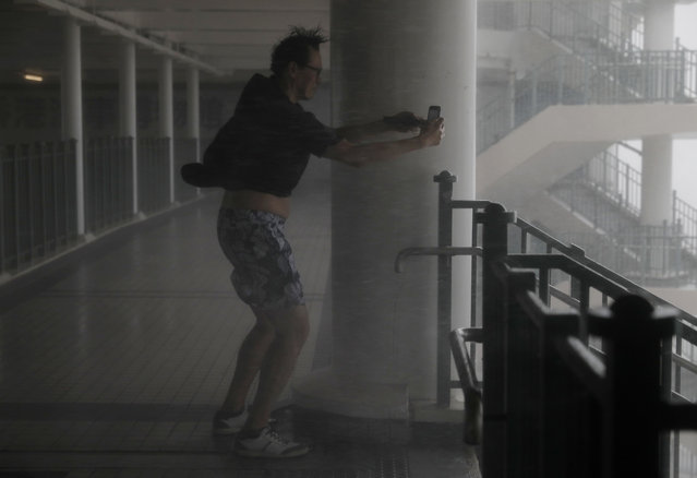 A man takes pictures against strong winds from Typhoon Mangkhut on the waterfront of Victoria Habour Hong Kong, Sunday, September 16, 2018. Hong Kong and southern China hunkered down as strong winds and heavy rain from Typhoon Mangkhut lash the densely populated coast. The biggest storm of the year left at least 28 dead from landslides and drownings as it sliced through the northern Philippines. (Photo by Vincent Yu/AP Photo)