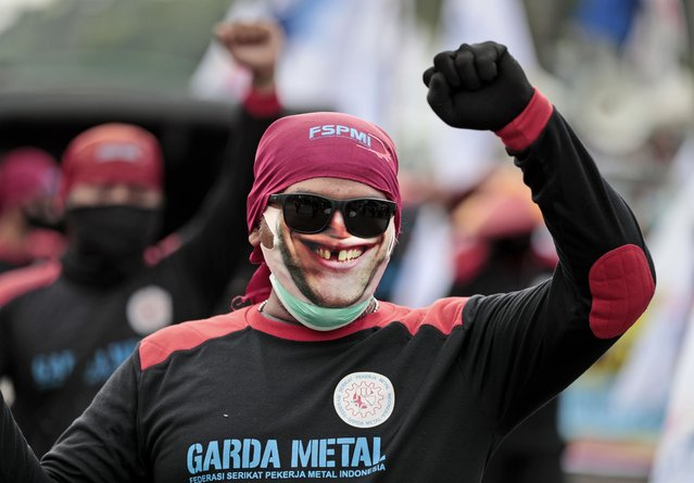 A worker wearing mask as a precaution against coronavirus outbreak, raises his fist as he shouts slogans during a May Day rally in Jakarta, Indonesia, Saturday, May 1, 2021. Workers in Indonesia marked international labor day on Saturday curtailed by strict limits on public gatherings to express anger at a new law they say could harm labor rights and welfare. (Photo by Dita Alangkara/AP Photo)