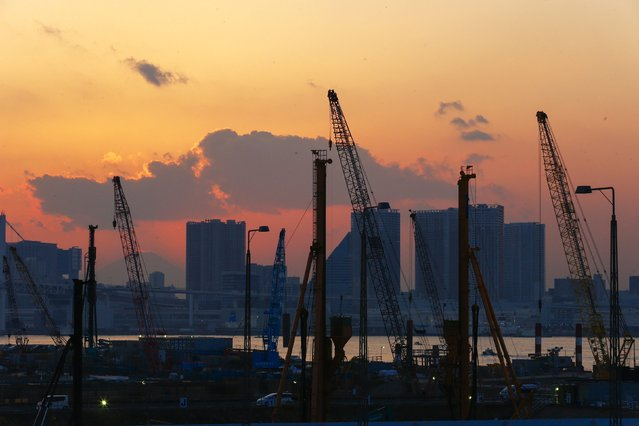 Cranes are pictures against the sunset at a construction site in the Toyosu district in Tokyo, February 12, 2015. (Photo by Thomas Peter/Reuters)