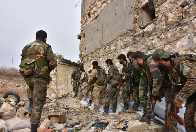 Syrian pro-government troops hold a position in Aleppo's eastern Karm al-Jabal neighborhood as they advance towards al-Shaar neighbourhood on December 5, 2016 during their offensive to retake Syria's second city. The Syrian Observatory for Human Rights said the advances of the Syrian and allied forces left the large Shaar neighbourhood encircled by government forces and in danger of falling from rebel control. With the capture of Shaar, the army would hold 70 percent of east Aleppo, four years after rebels first seized it. (Photo by George Ourfalian/AFP Photo)