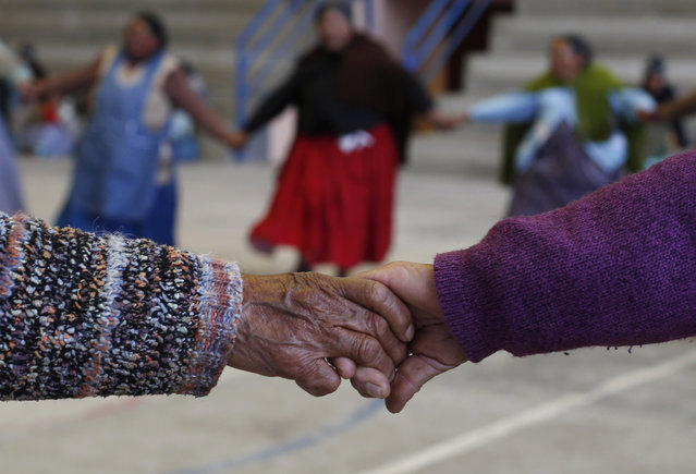 """In this January 28, 2105 photo, elderly Aymara indigenous women warm up before playing handball in El Alto, Bolivia. """"There are days my knees hurt from rheumatism, but when I play it goes away"""", said 77-year-old Rosa Lima, who first began doing simple exercises eight years ago, then later took up team handball. She lives alone and looks forward to playing with her friends every week. (Photo by Juan Karita/AP Photo)"""